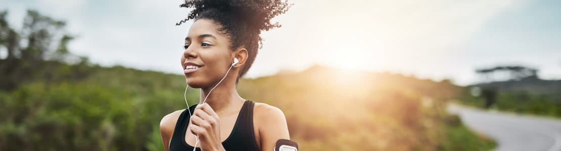 Woman running outside with headphones on