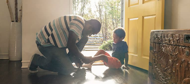 Man putting on his son's shoes in front of an open door