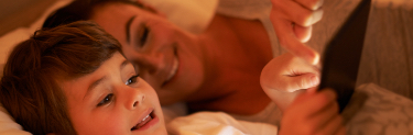 Mother and child reading tablet screen while lying in bed smiling