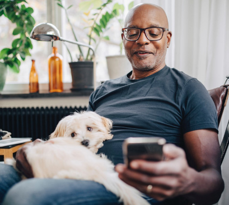 Man with a dog on his lap while looking at his phone smiling