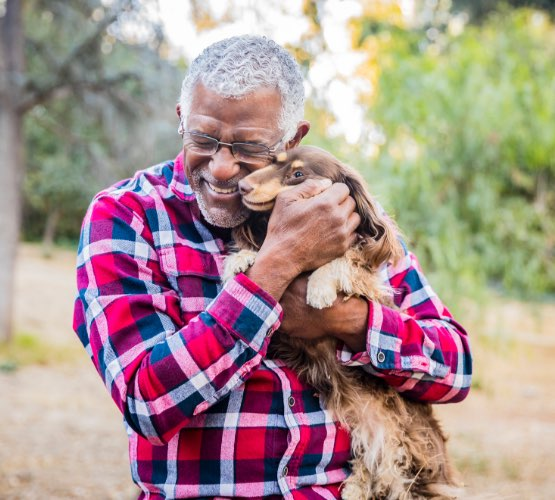 Senior wearing glasses hugging dog